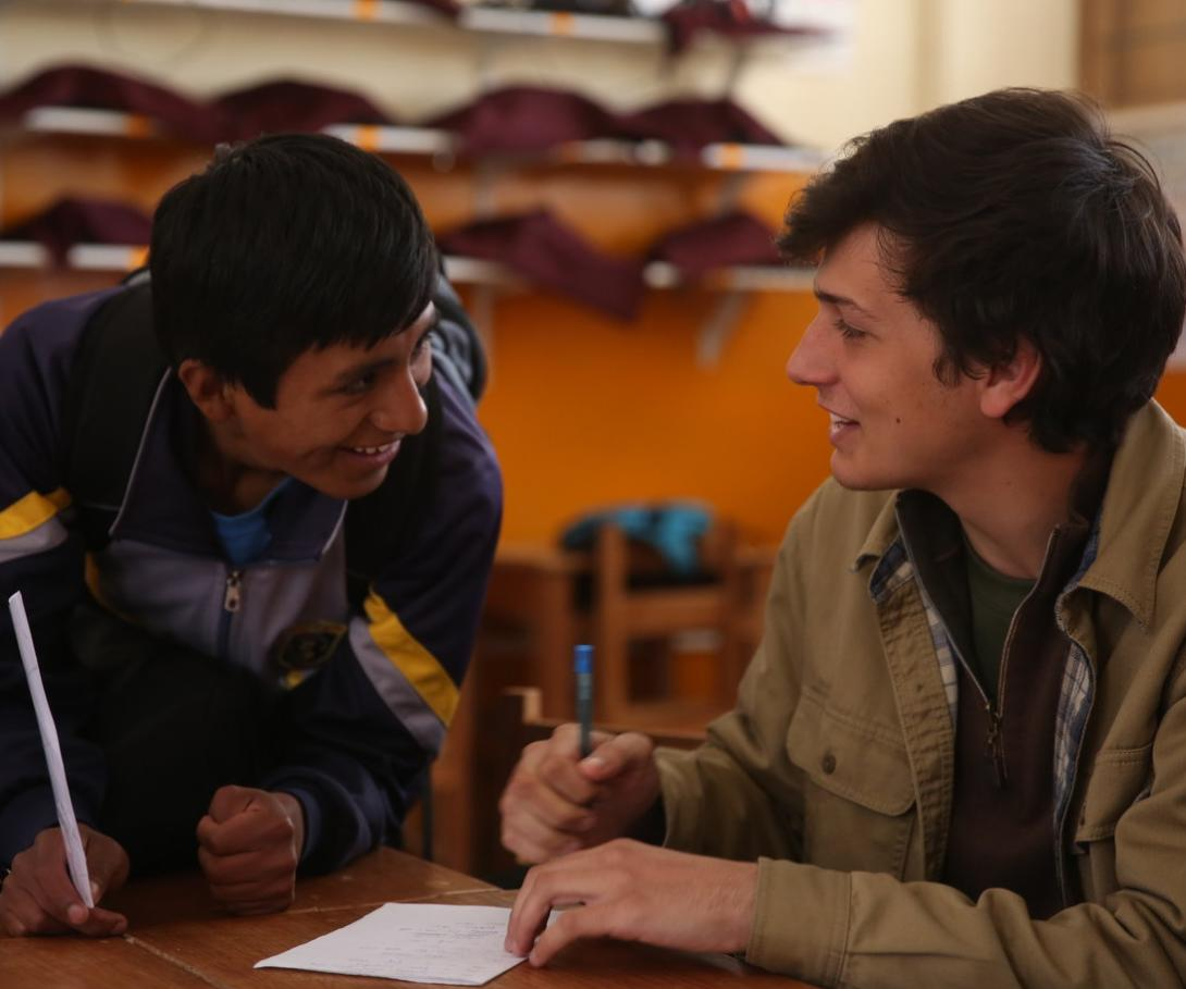 A volunteer teaching English in Peru chats to a student between classes.